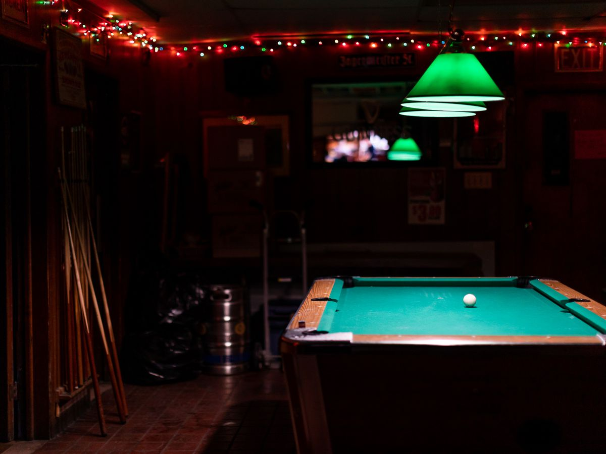 a pool table with a green lamp over the top and a dark room with christmas lights strung around the edge