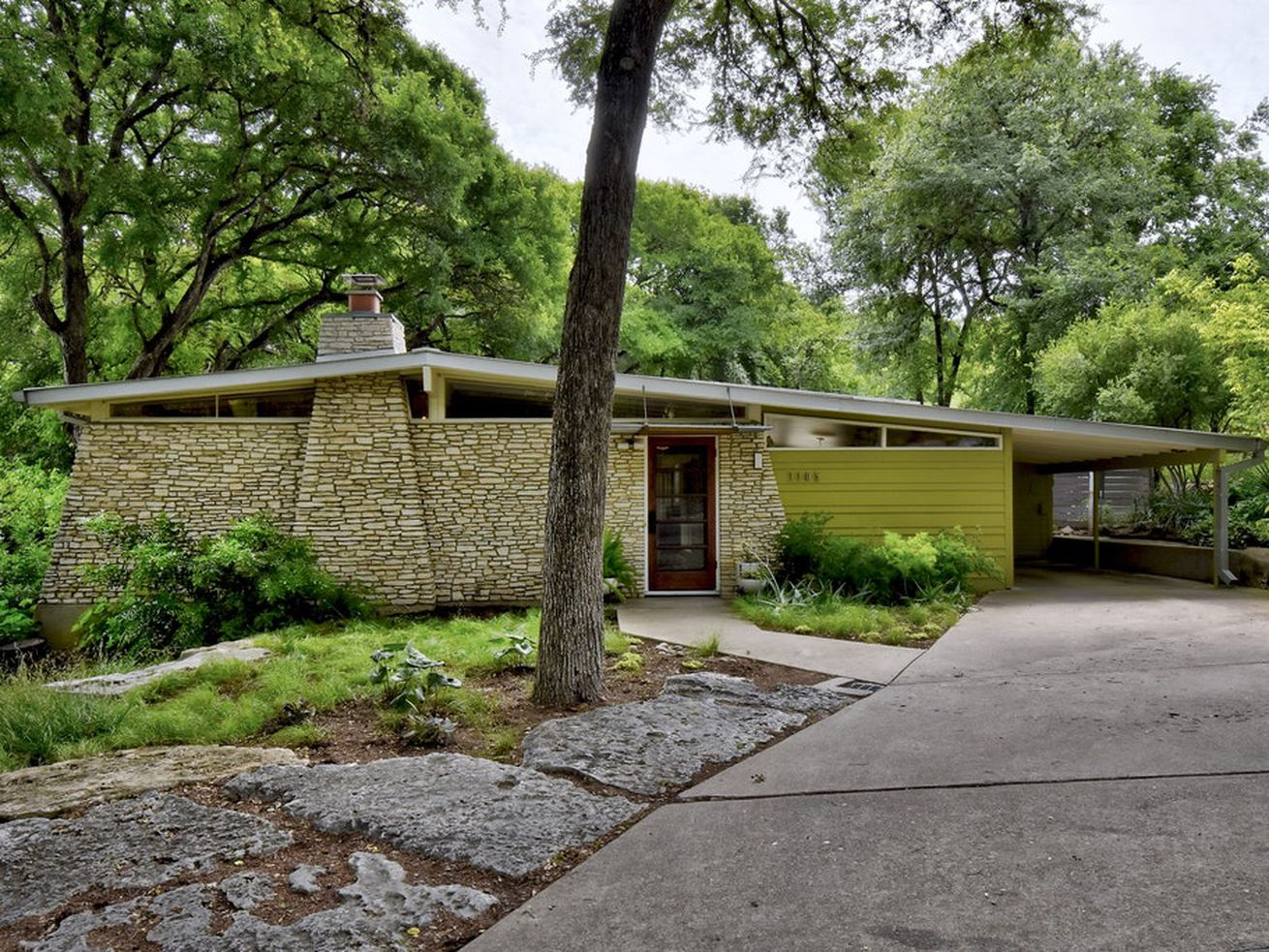 An exterior view of a midcentury modern house in Austin. There is a concrete driveway, a stone wall, and a green exterior wall.