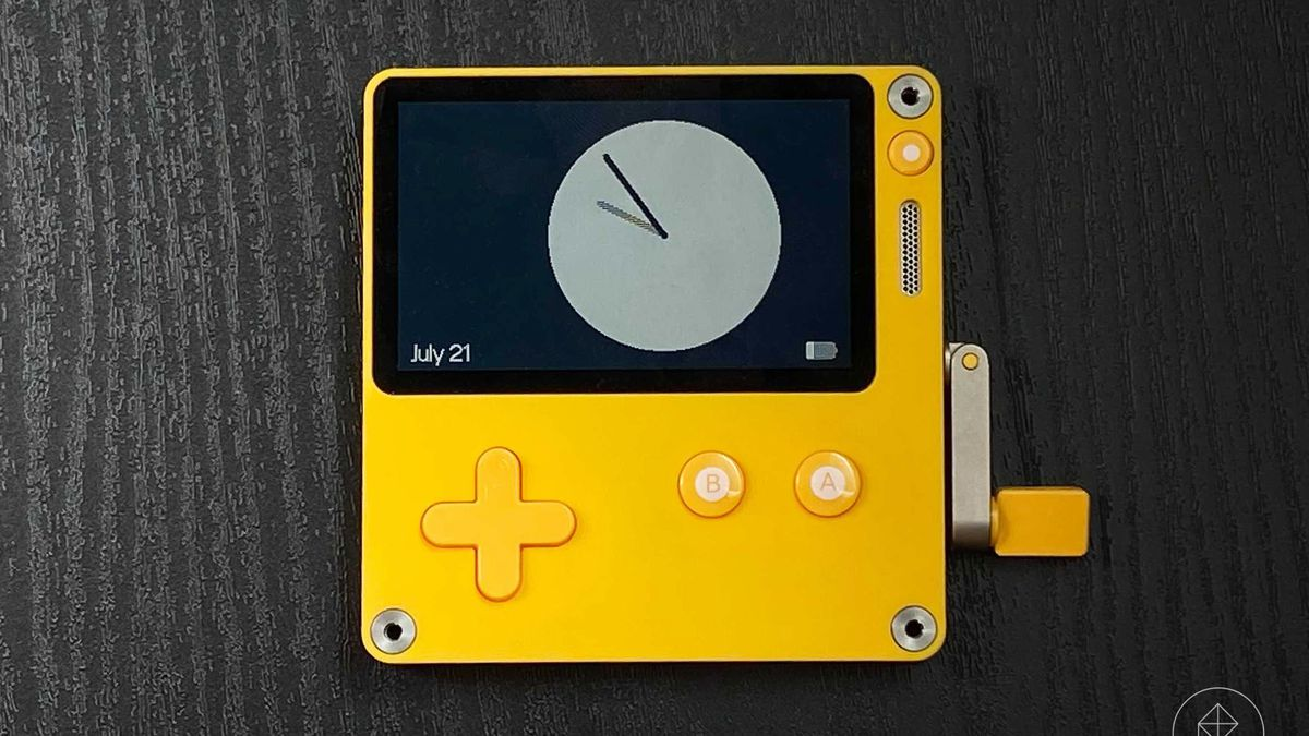 A Playdate rests on a black surface. A clock without numbers ticks on the screen.