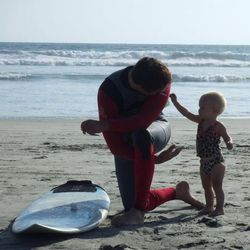 Greg Trimble takes a break from surfing to play with his daughter.