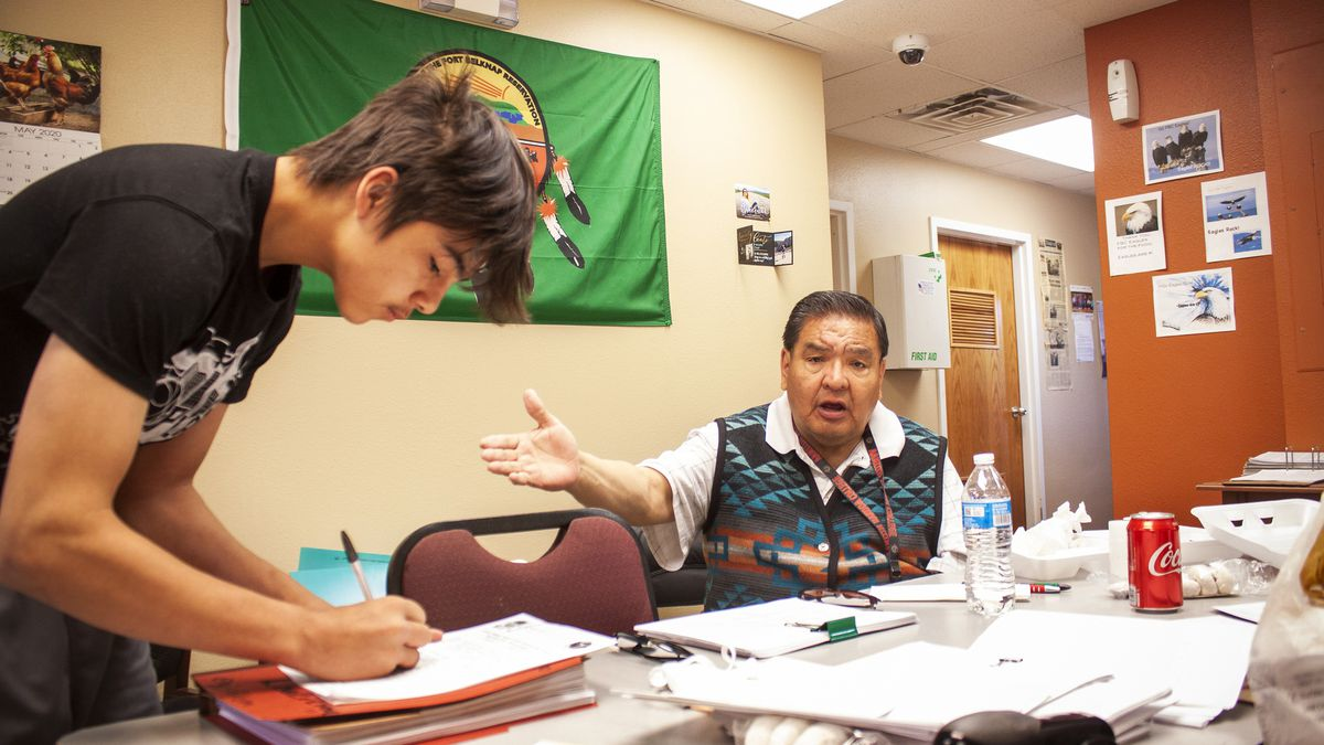 """Gerald """"Bear Shirt"""" Stiffarm is pictured with a volunteer in his office on the Fort Belknap Indian Community in Montana."""