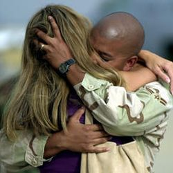 """Airman 1st Class Rawn Sahai embraces his wife, Nikol, after getting off a chartered jet at Hill Air Force Base Monday. """"It was hot,"""" he said. """"It was a lot of work, put in a lot of hours. But everyone was focused on the mission."""""""