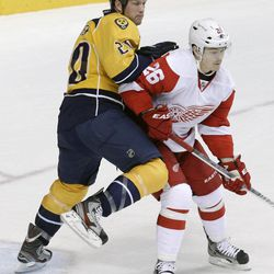 In this April 20, 2012 photo, Nashville Predators defenseman Ryan Suter (20) plays against Detroit Red Wings left wing Jiri Hudler (26), of Czech Republic, during the Predators' 2-1 win in Game 5 of a first-round NHL hockey playoff series in Nashville, Tenn. Suter, goalie Pekka Rinne, of Finland, and defenseman Shea Weber are key reasons Nashville will be playing in the second round of the Western Conference playoffs, with sights set on making a deep run this postseason.