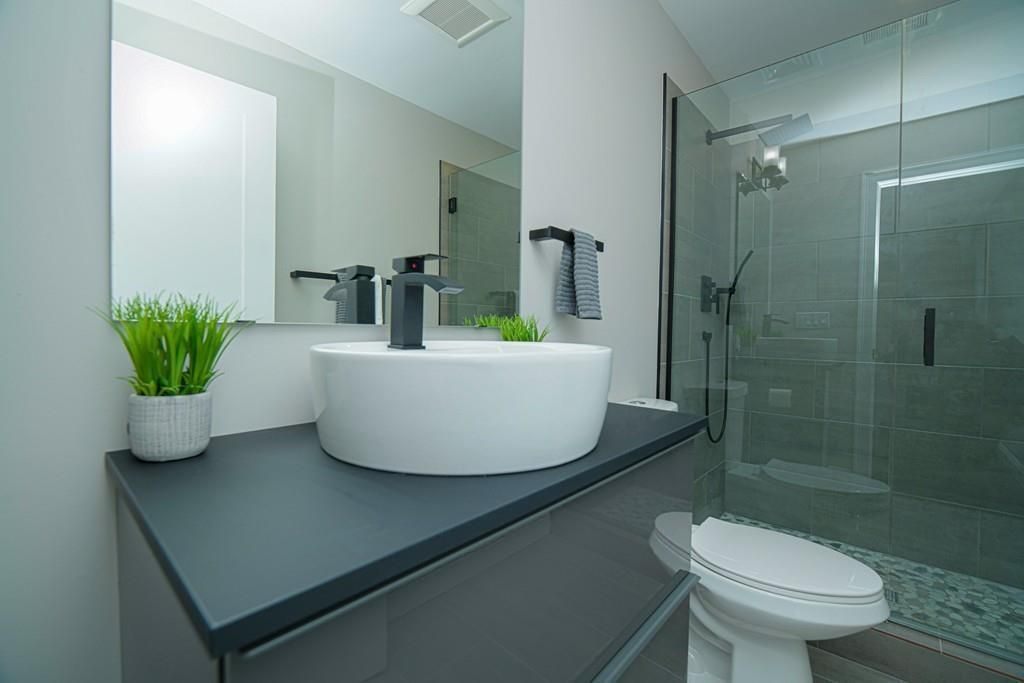 A bathroom with a basin sink and a glass-enclosed shower.
