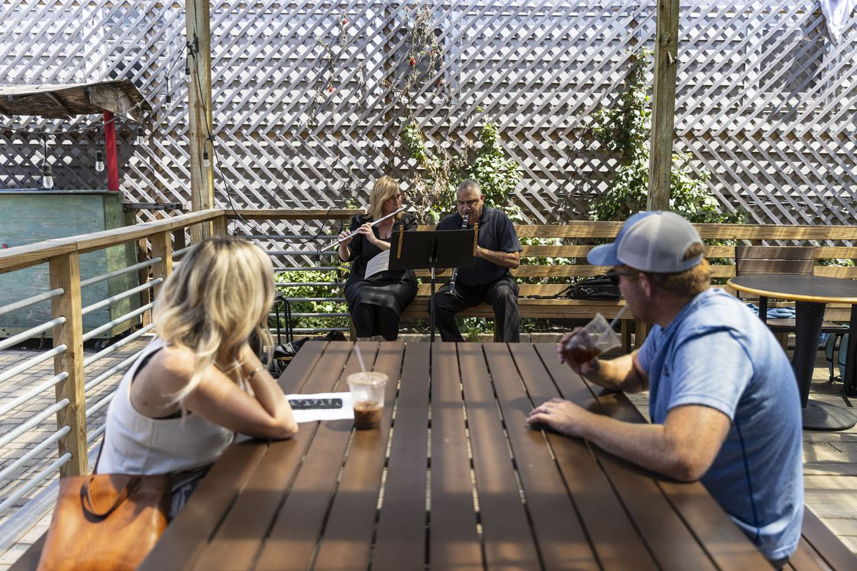 Sheila, left, and Dale West, right, listen to Janice MacDonald, center left, and Dileep Gangolli, center right, of the Chicago Sinfonietta play outside at the Back of the Yards Coffeehouse at 2059 W 47th St in Back of the Yards, Thursday, Aug. 5, 2021.