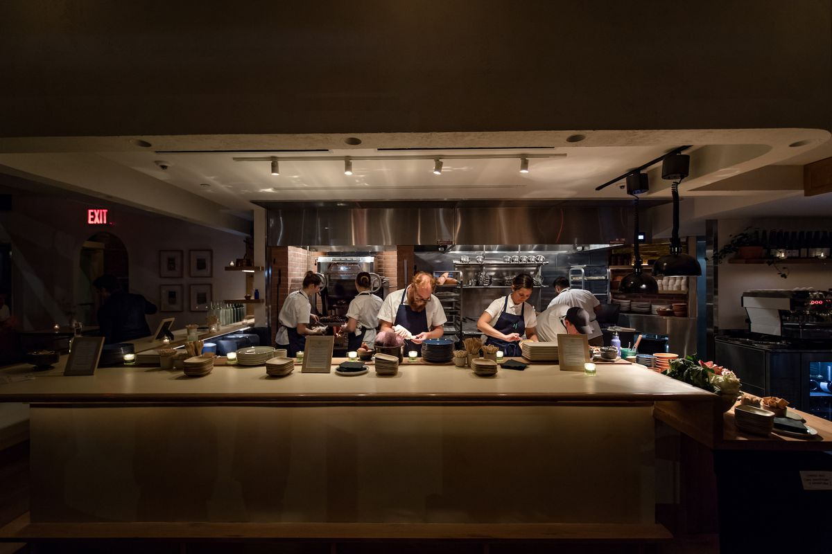 Chefs working behind a gray counter in dark lighting at 232 Bleecker