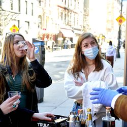 Curious customers participate in a sidewalk tasting at Spirited Away, an alcohol-free bottle shop, in the Lower East Side of Manhattan in New York on Saturday, March 13, 2021. The shop is devoted to everything needed to make alcohol-free cocktails.