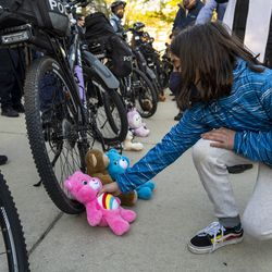 A young child, leaves stuffed animals at the tires of a Chicago police officers bike, which is being used as a shield to prevent activists from getting closer to the Chicago Police Training Academy, Friday, April 30, 2021.