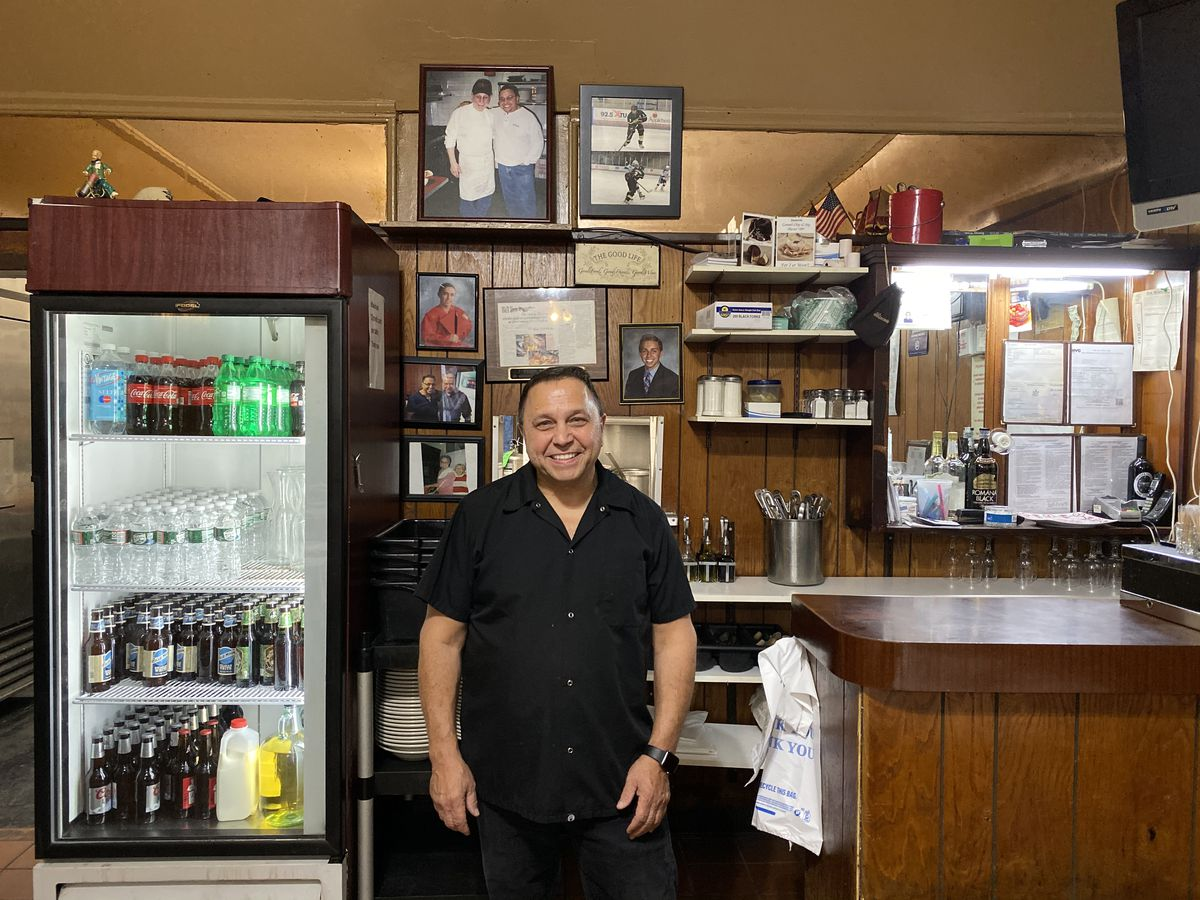 Owner Anthony Catapano, wearing a black shirt, stands near the cash register and wood-paneled counter at Two Toms