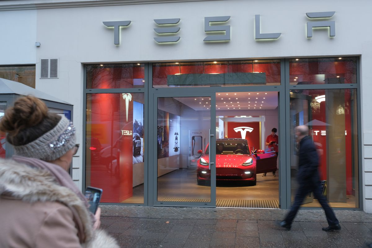 Pedestrians walk past a Tesla storefront featuring a Model 3 in the window.