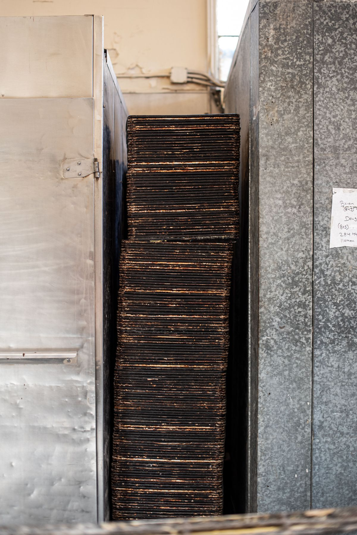 A pile of aging pans between ovens inside of an old bakery.