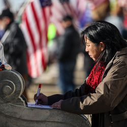 """Susan, who did not provide a last name, writes on a sign """"Stolen: My right to a fair legal election"""" near the steps of the Capitol in Salt Lake City on Wednesday, Jan. 6, 2021."""