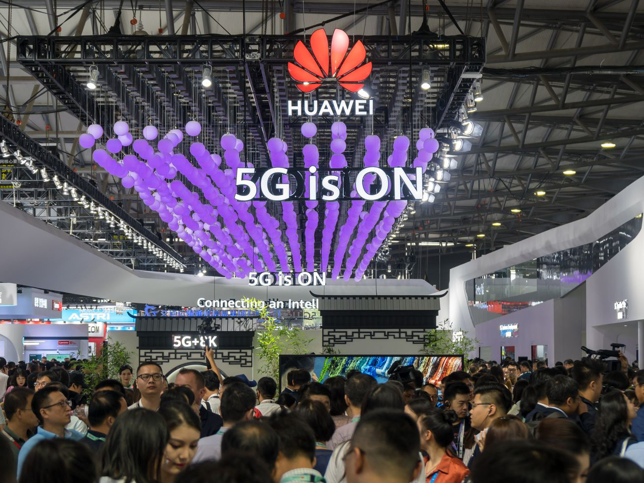 """A crowd of attendees at the Mobile World Congress under a sign reading """"Huawei: 5G is ON."""""""