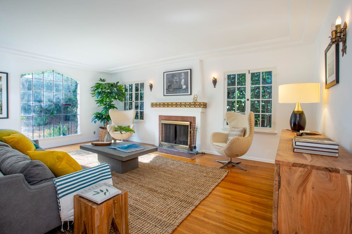 Bright living room with casement windows, fireplace, and a gray coffee table and sofa.