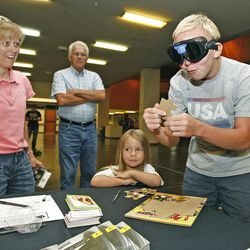 """Michael Atkinson, 15, tries to put together a puzzle while wearing """"Fatal Vision"""" goggles that simulate impairment from drinking while his mom, Patti Atkinson, and sister, Taylor, watch."""