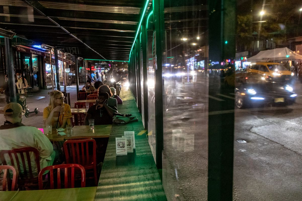 Patrons sit along Ninth Avenue in a green patio with an awning and red chairs