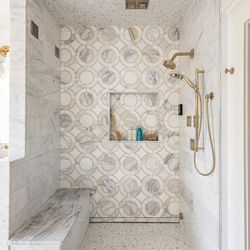 The main bath's shower—its door not yet installed—is equipped with a rainhead, body sprays, a handheld shower, and steam. Three styles of marble tile add interest to the walls and floor. <em>Shower drains: </em><a class=