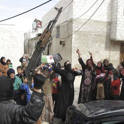 In this Sunday, April 1, 2012 photo, Syrians chant slogans against President Bashar Assad upon the arrival of the Free Syrian Army in a neighborhood of Damascus, Syria.