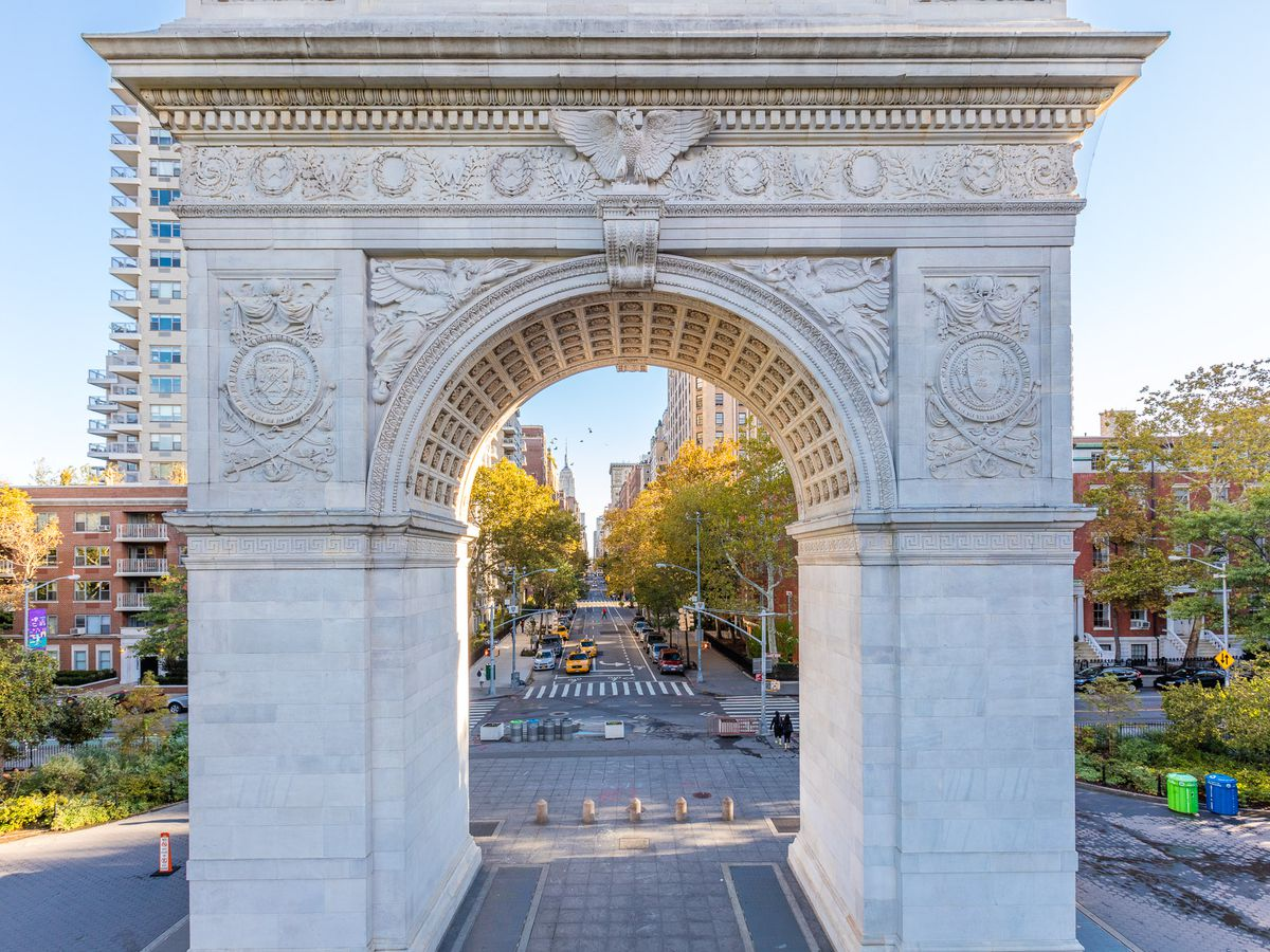 The Washington Square Arch in Washington Square Park, New York City. The arch is white with ornamentation. The view through the arch is a city street, trees, and buildings.