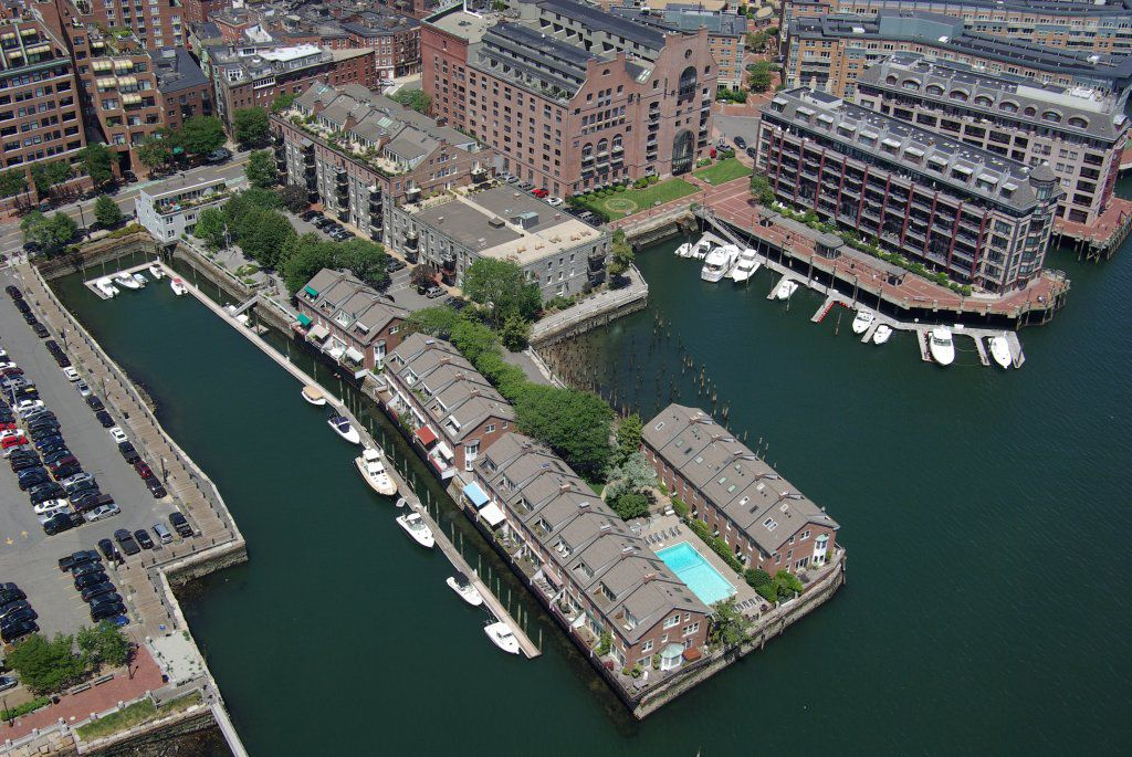 An aerial view of a waterfront. One of the piers has a swimming pool on it.