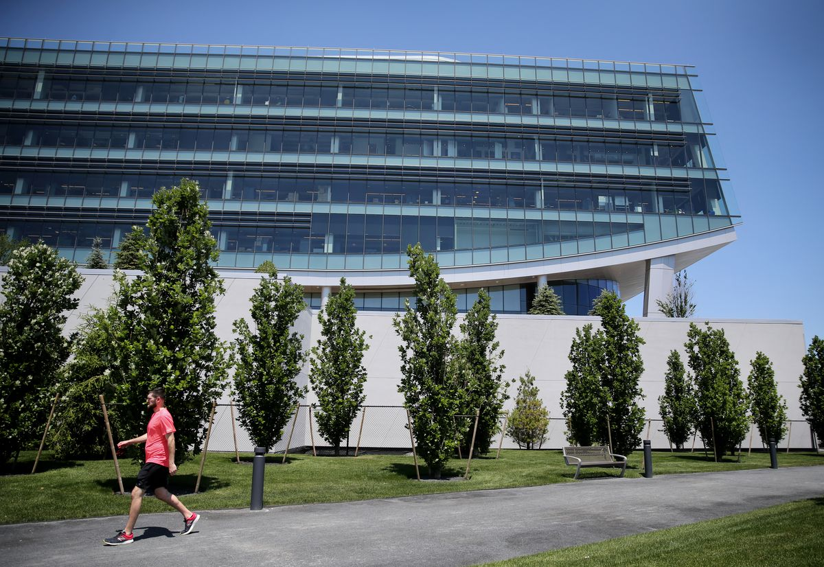A kind of curvy-looking rectangular glass building with a walker in front of it and trees between the walker and the building.
