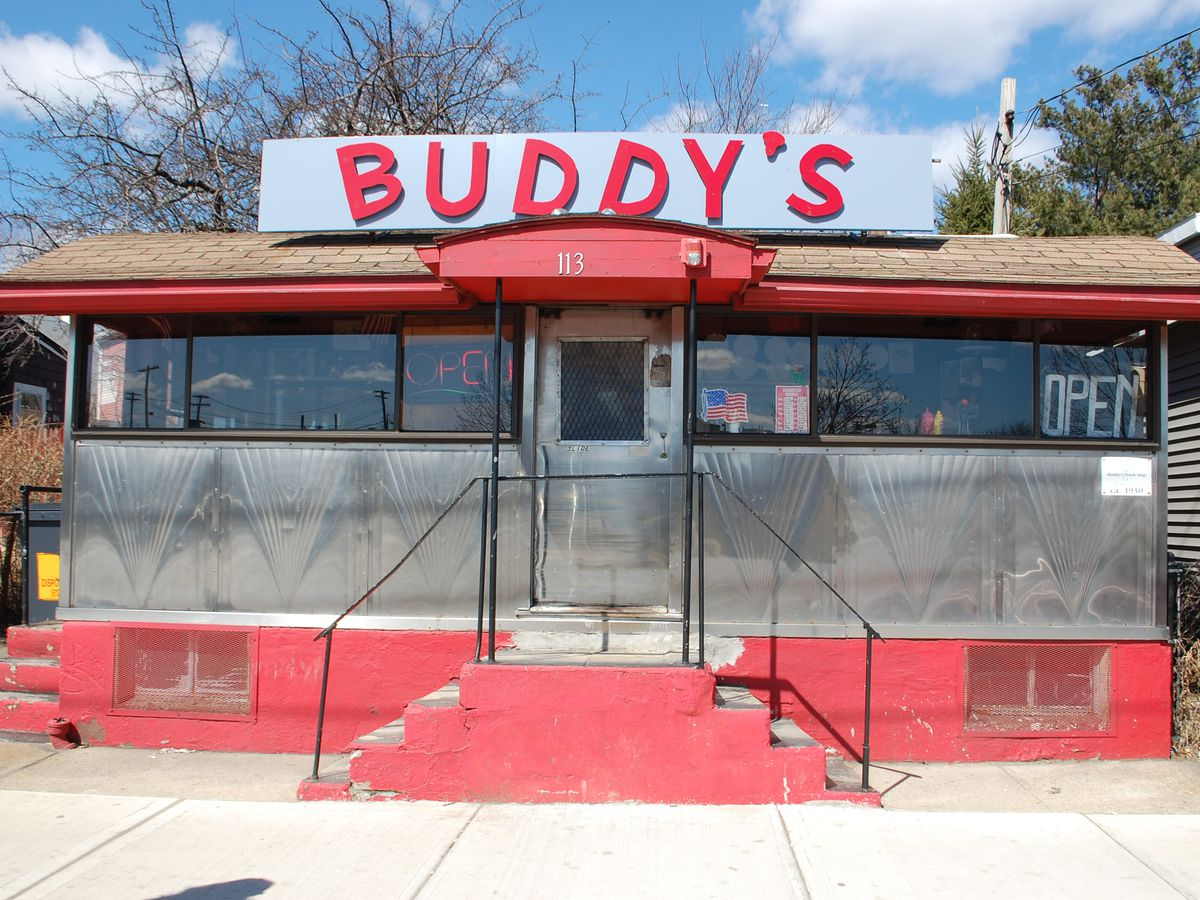 """Front view of a small classic diner car during the day. A sign on top reads """"BUDDY'S"""" in red lettering, and the diner has red accents."""