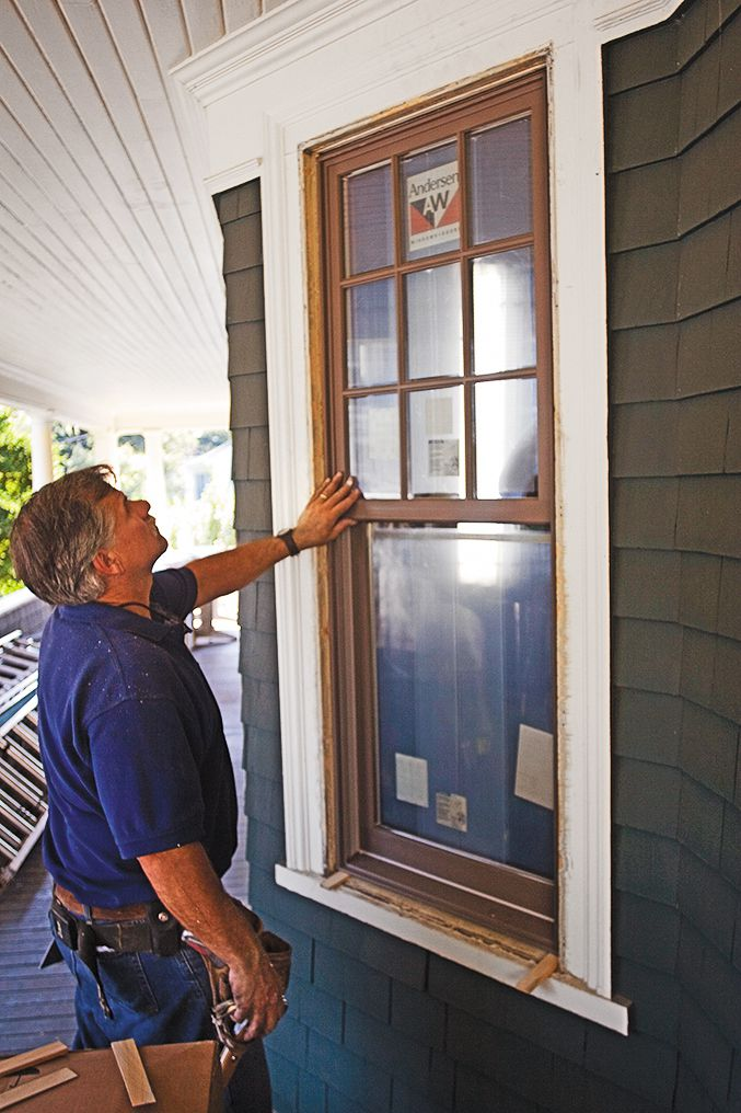 Man Stands In Front Of Window Replacement To Find Gaps