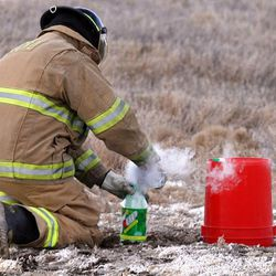 Salt Lake Police Department Bomb Squad technician Dave Layton prepares to put a homemade dry-ice bomb under a 5-gallon plastic bucket during a demonstration Tuesday to raise awareness of the dangers associated with homemade dry-ice and chemical bombs.