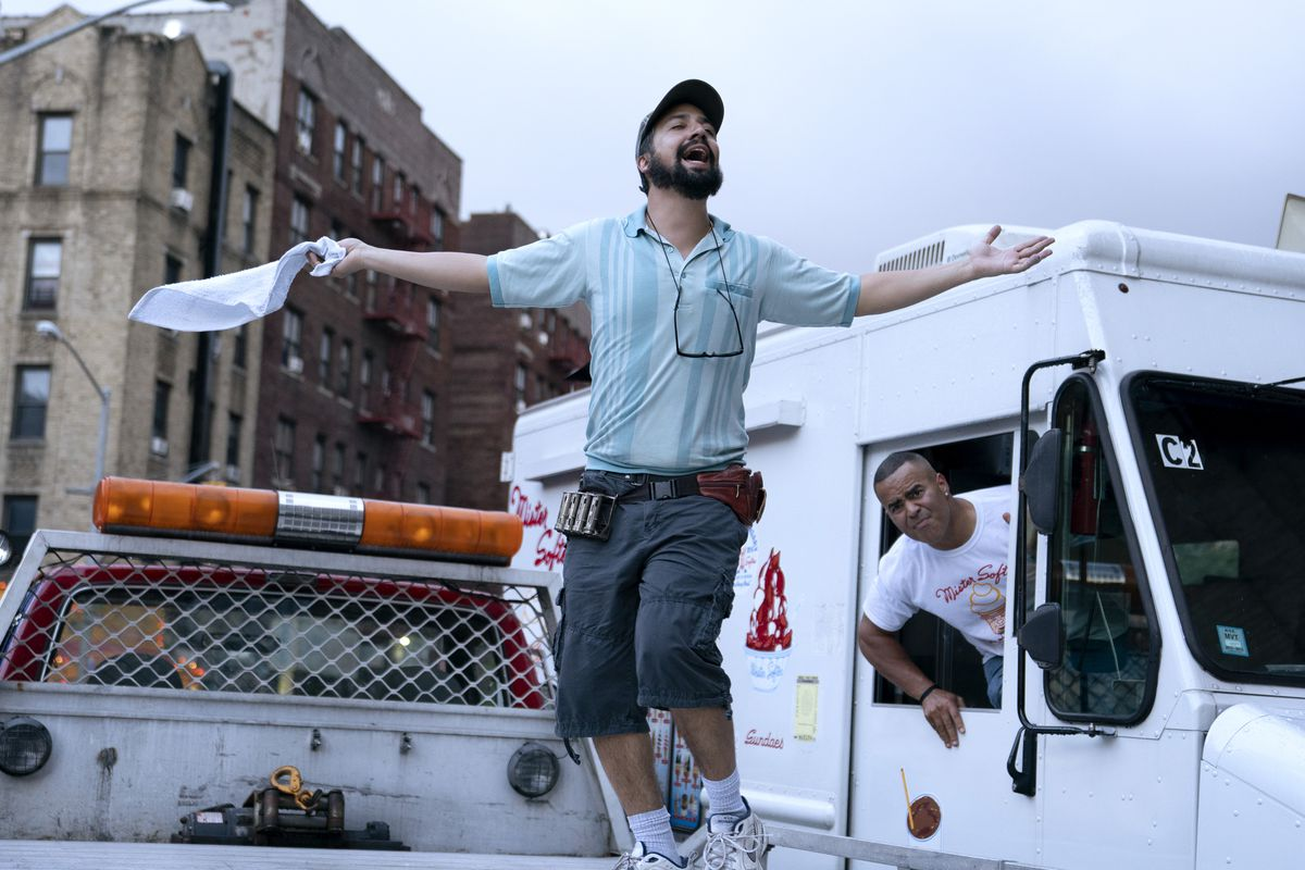 Lin-Manuel Miranda stands on the back of a truck and sings with arms outstretched in a scene from In the Heights
