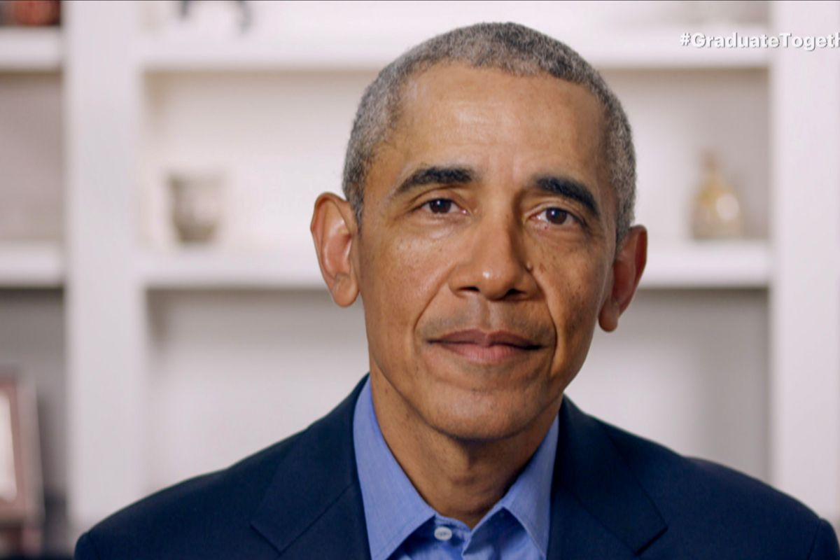 Obama, in a dark suit and blue shirt with an open collar, speaks while seated in a well-lit room. Behind him is a sparse bookshelf, its knickknacks out of focus.