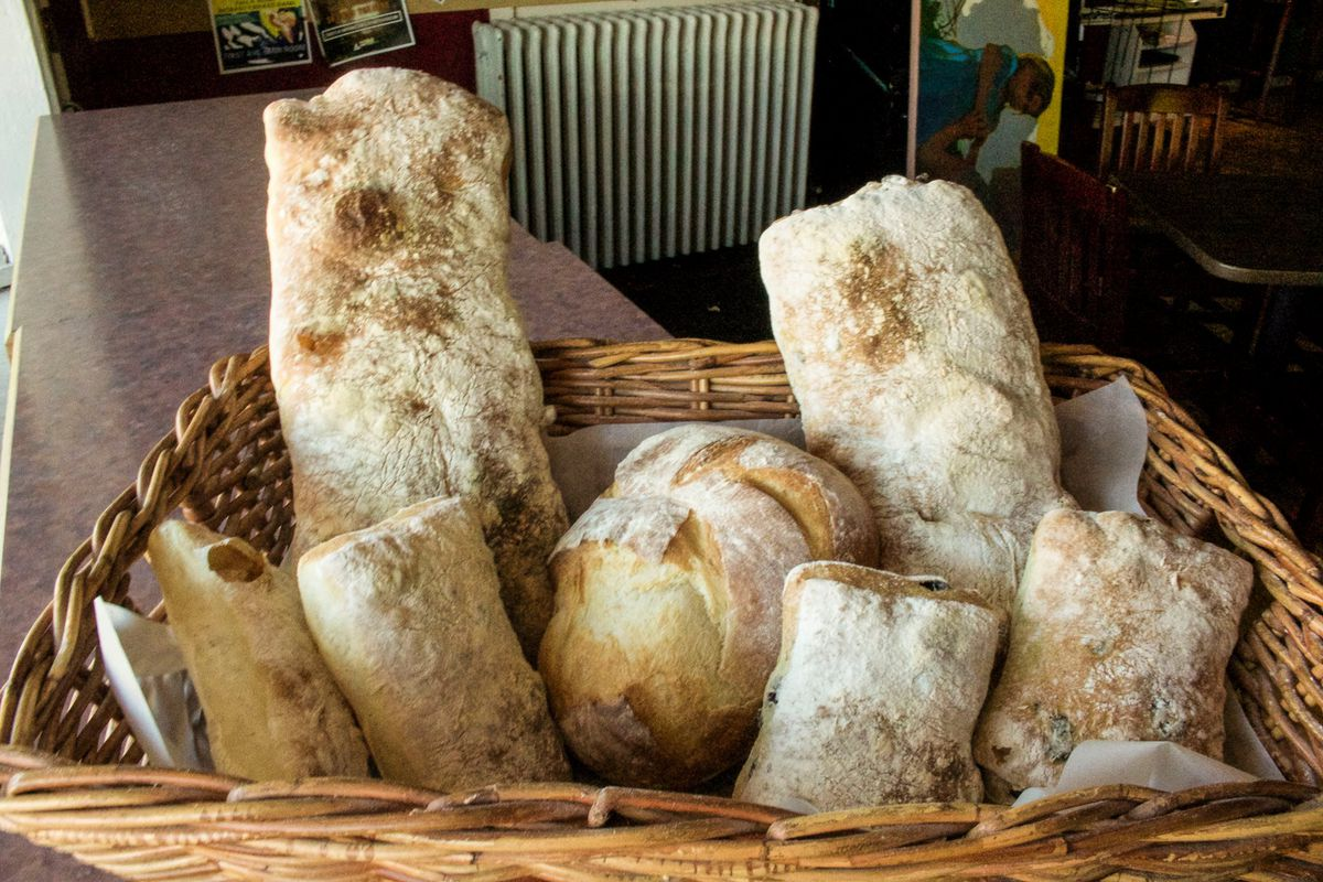 A basket filled with flour dusted bread loaves of different shapes and sizes.
