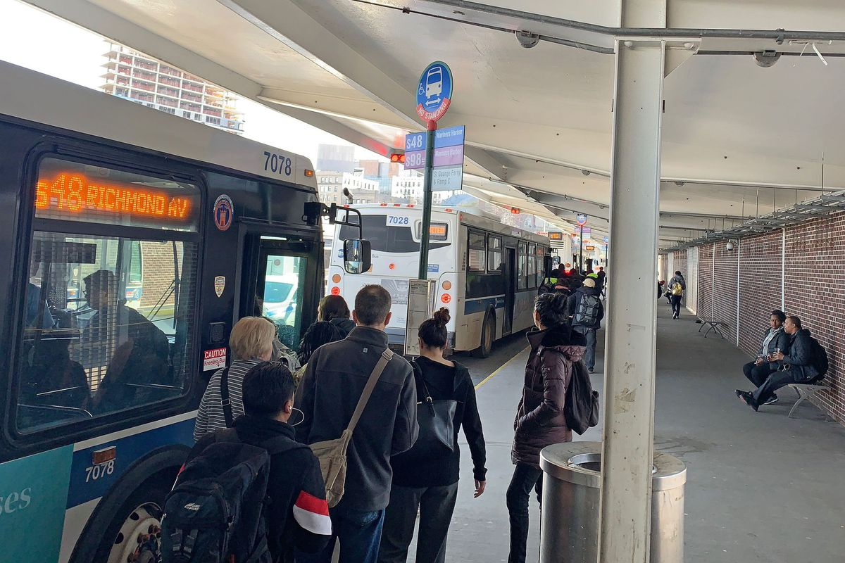 Commuters board buses at the St. George Ferry Terminal, April 9, 2019.