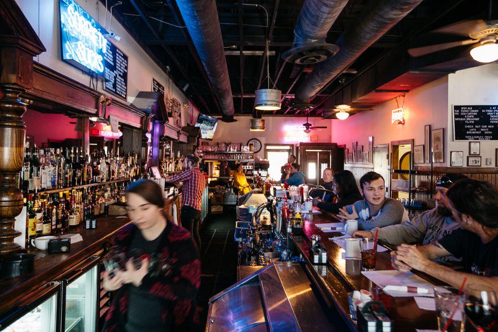 An employee at Honest John's walks behind the bar.