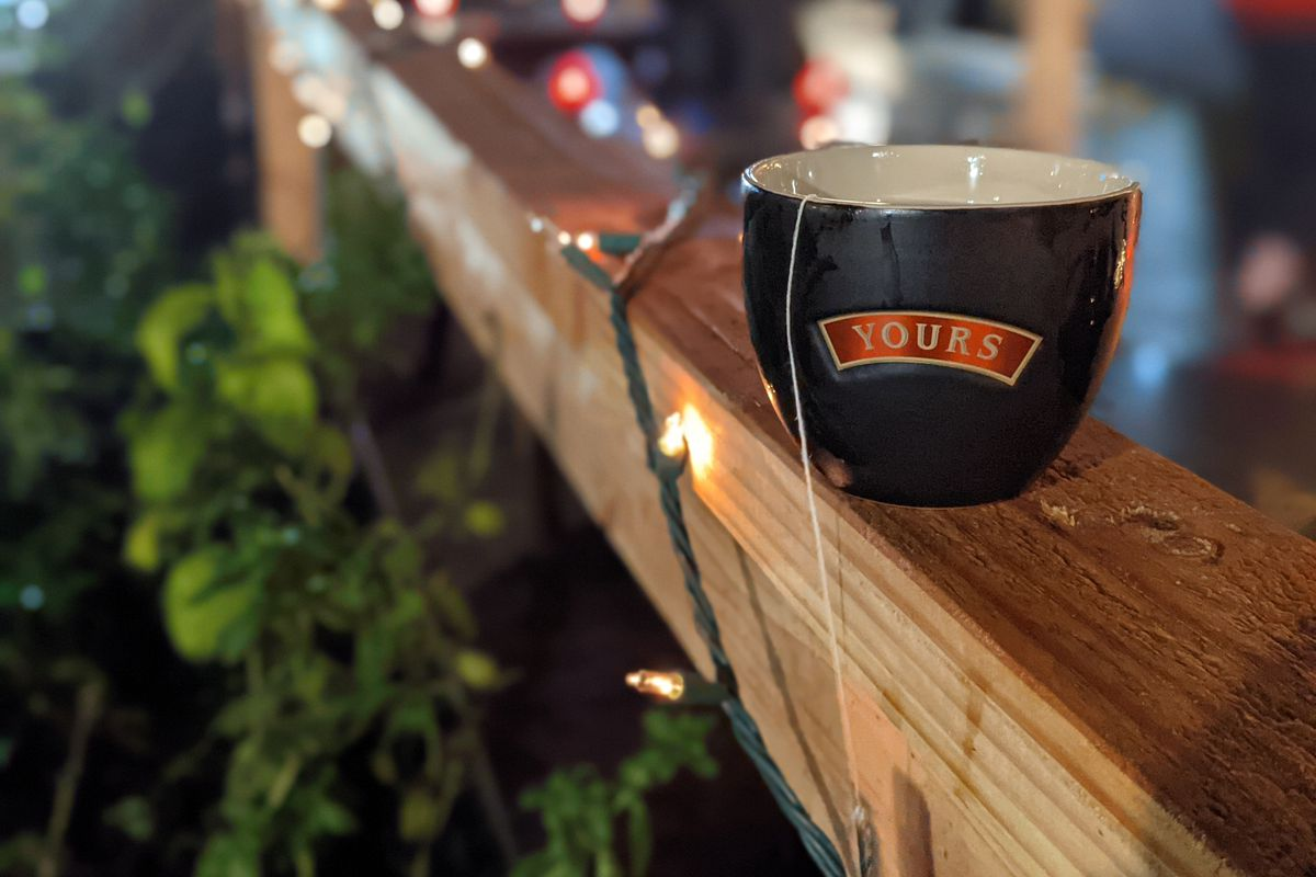 """A black mug with the word """"Yours"""" inscribed on it sits on a wooden beam wrapped in white Christmas lights. The tassel of a teabag hangs from it."""