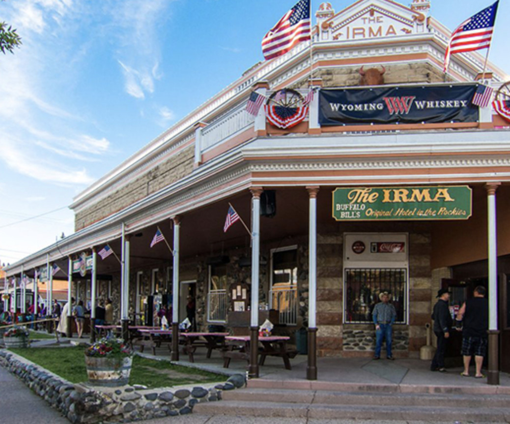 An old-time western-style exterior with signage for the Irma Hotel.