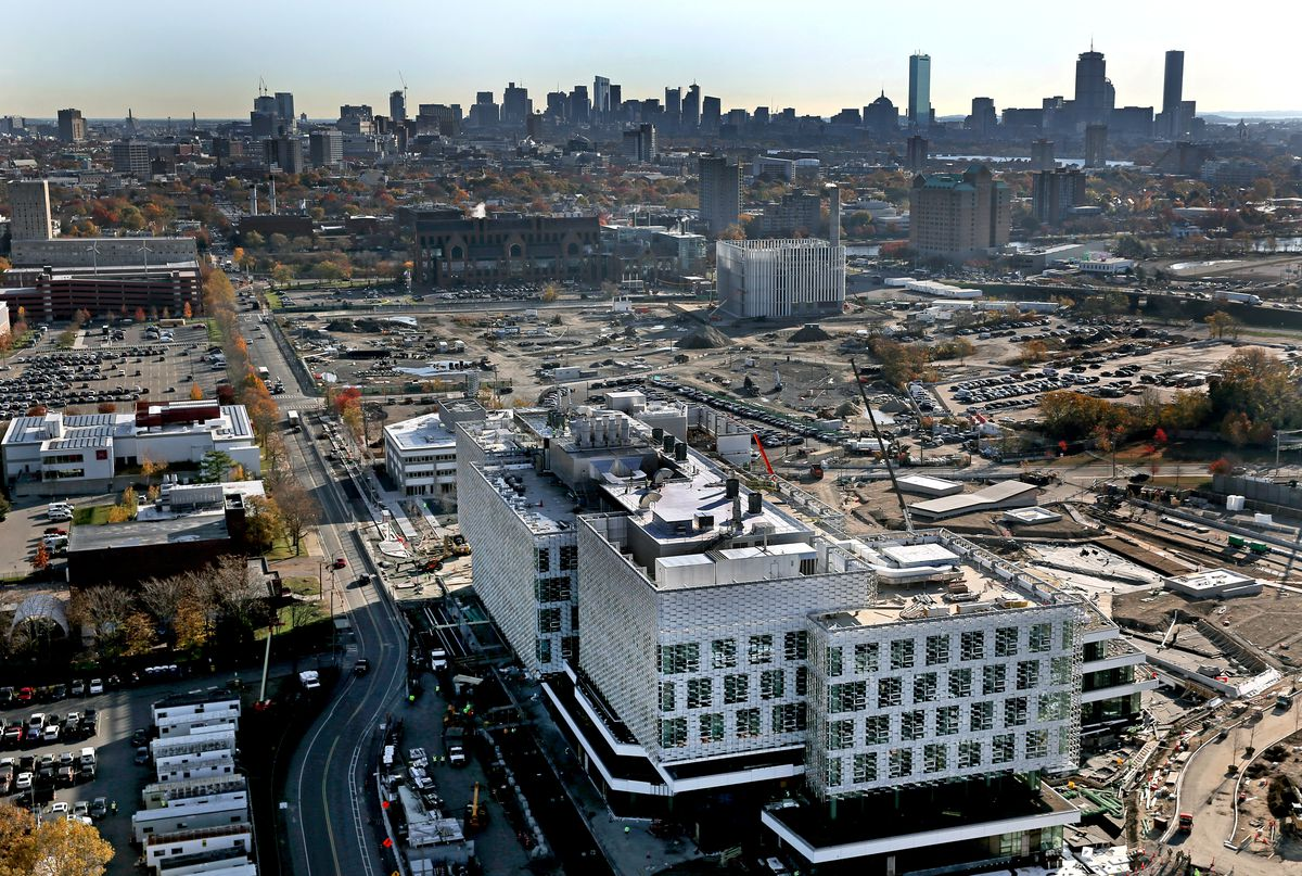 An aerial view of a large construction site, with one building up, and a city skyline in the background.
