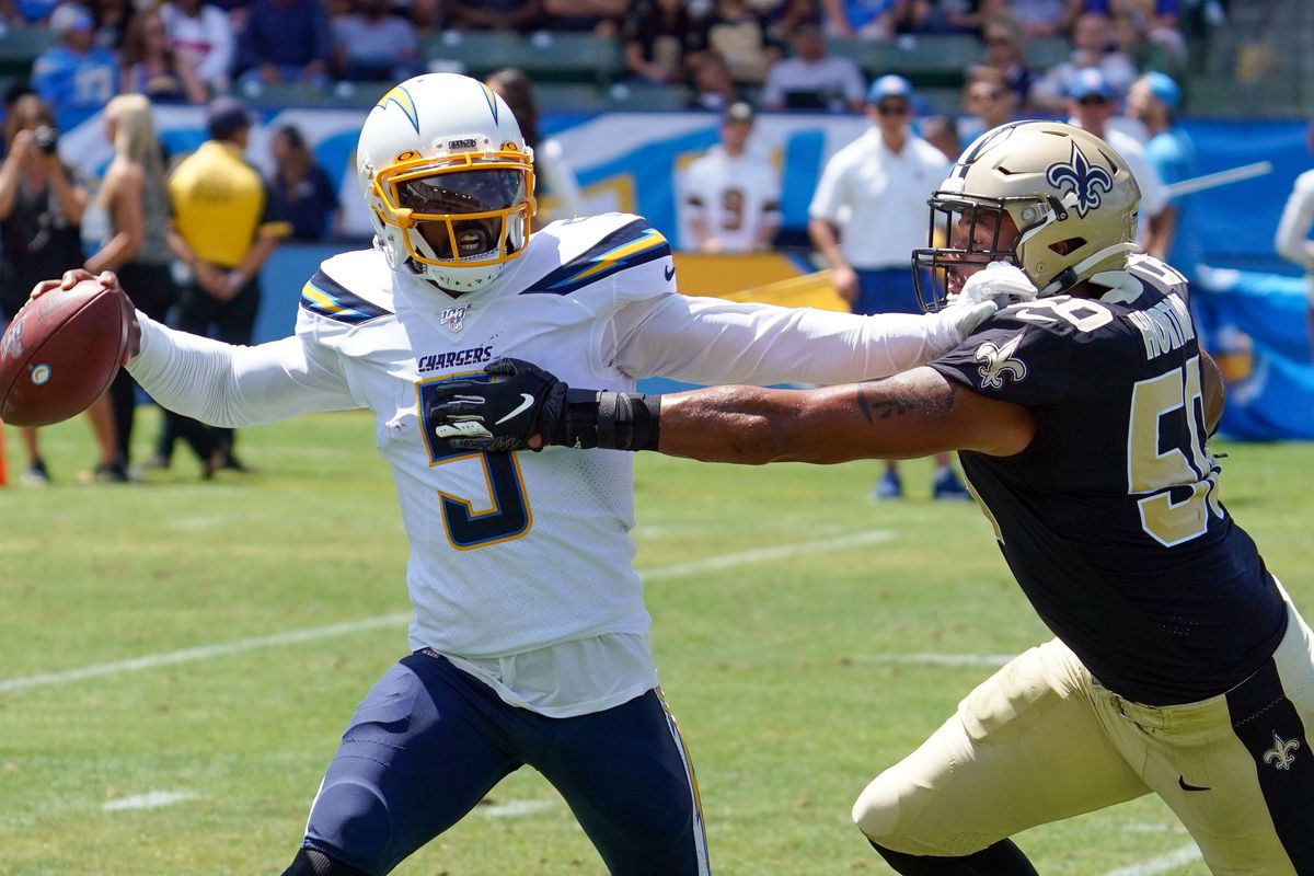 Los Angeles Chargers quarterback Tyrod Taylor throws the ball as he's pressured by New Orleans Saints defensive end Wes Horton in Carson on Sunday, Aug. 18, 2019.
