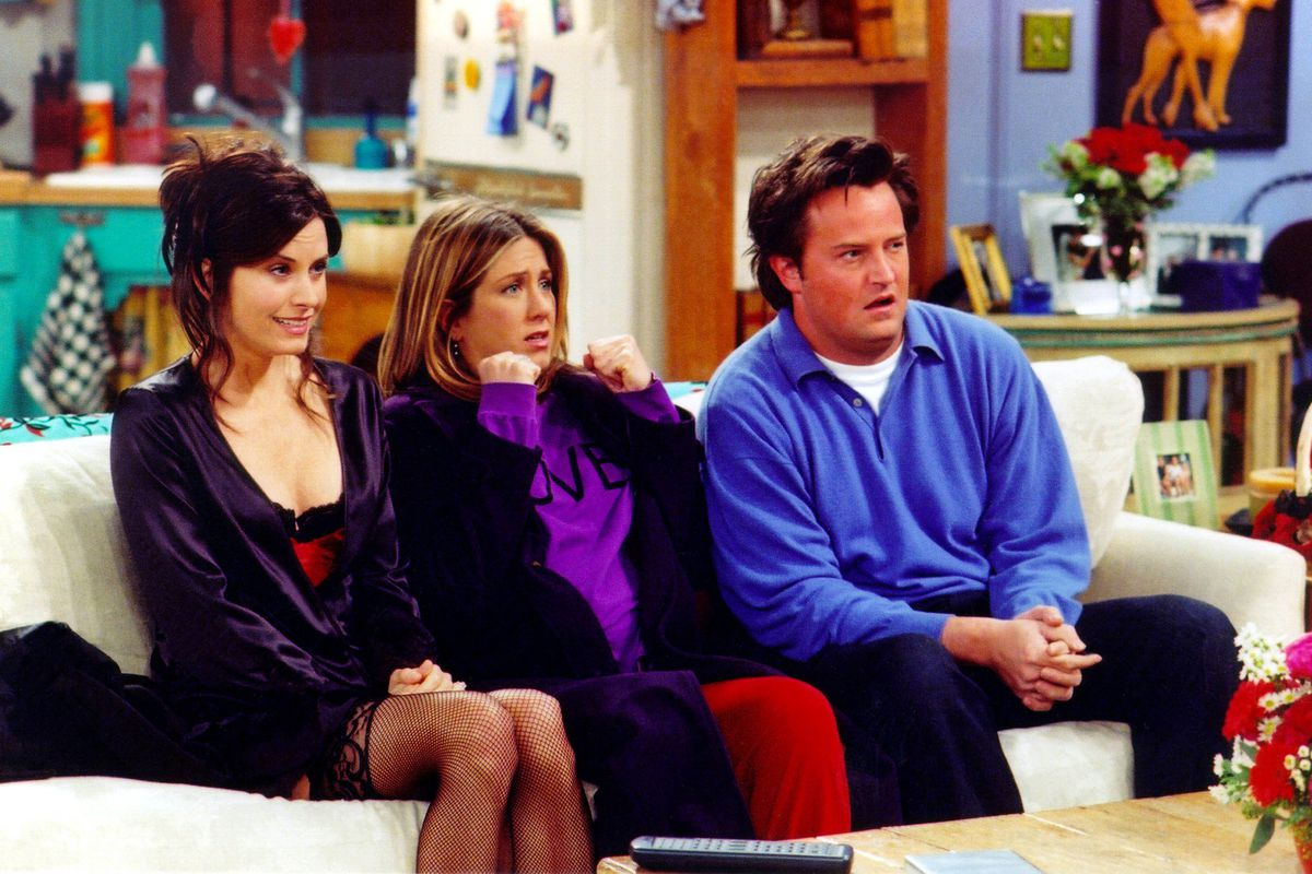 """Three of the cast members from the TV show """"Friends"""" sitting on a couch"""