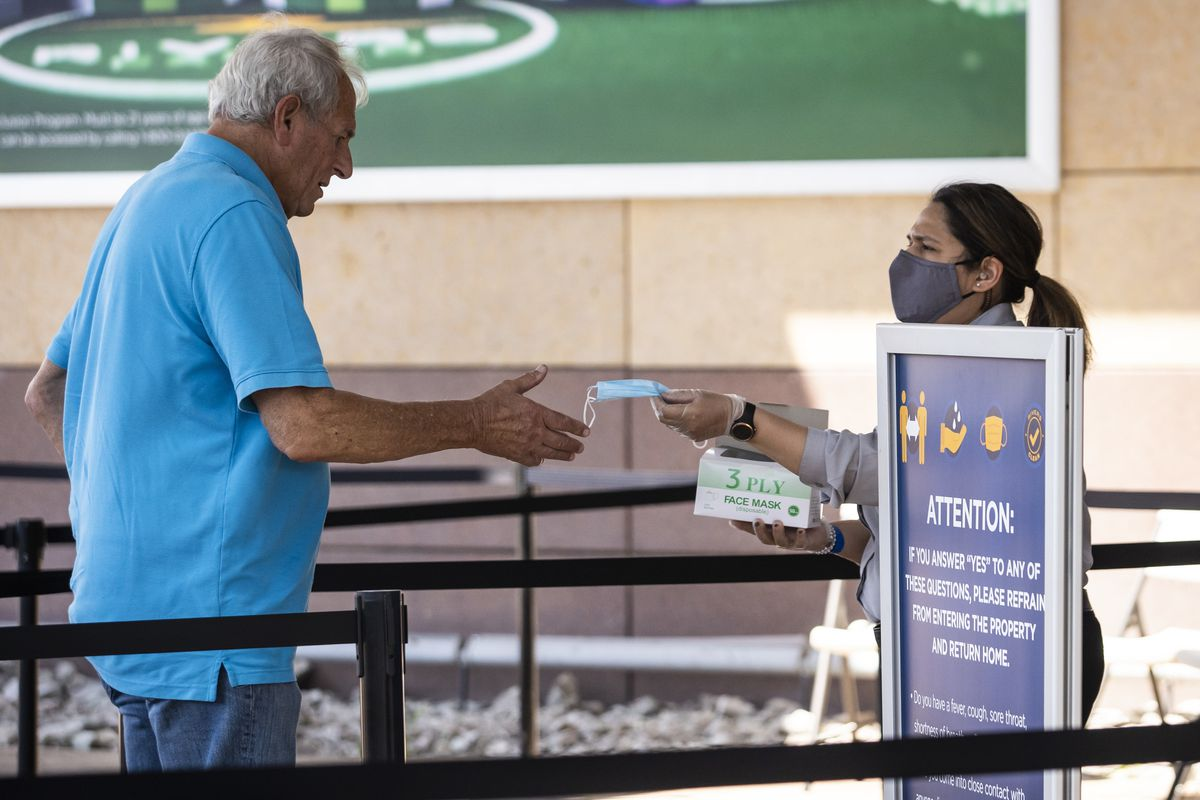 A security guard stationed at the front door gives a face mask to a guest before he can enter Rivers Casino in Des Plaines on the first day of reopening following July 1.