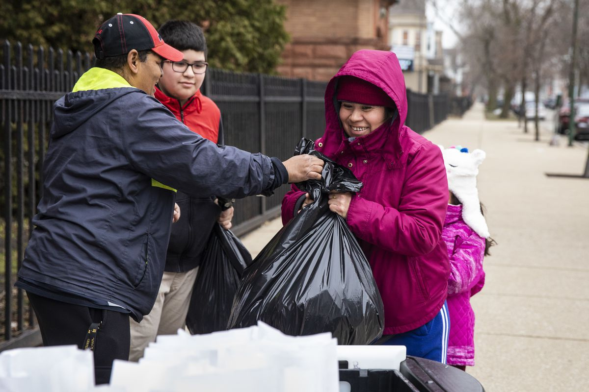 Estella Damien, 45, and her two children, 11-year-old Anthony Ora and 7-year-old Janelli Roa, receive three days of free breakfast and lunch meals for each student at William P. Nixon Elementary School, 2121 N. Keeler Ave., Thursday morning, March 19, 2020. All Illinois schools, including Chicago Public Schools, are closed for weeks amid fears of the coronavirus pandemic.