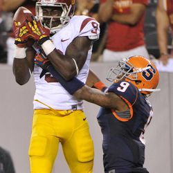 Southern California wide receiver Marqise Lee, left, catches a touchdown pass over Syracuse cornerback Ri'Shard Anderson during the fourth quarter of an NCAA college football game Saturday, Sept. 8, 2012, in East Rutherford, N.J. USC defeated Syracuse 42-29.