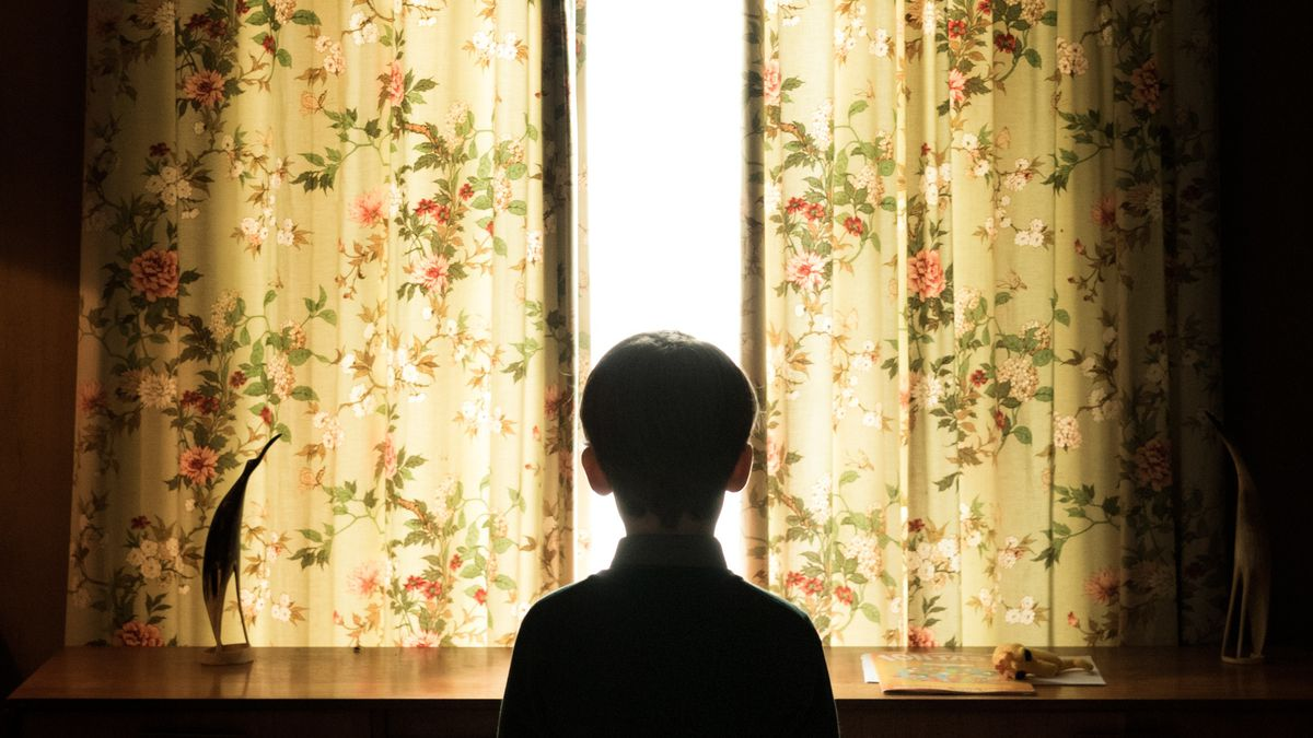 A young boy stands in silhouette against a window with floral curtains partially open.