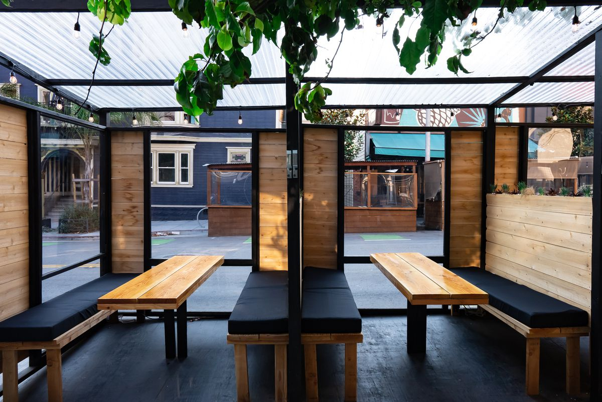 A warm wooden parklet with bench seating and black metal accents.