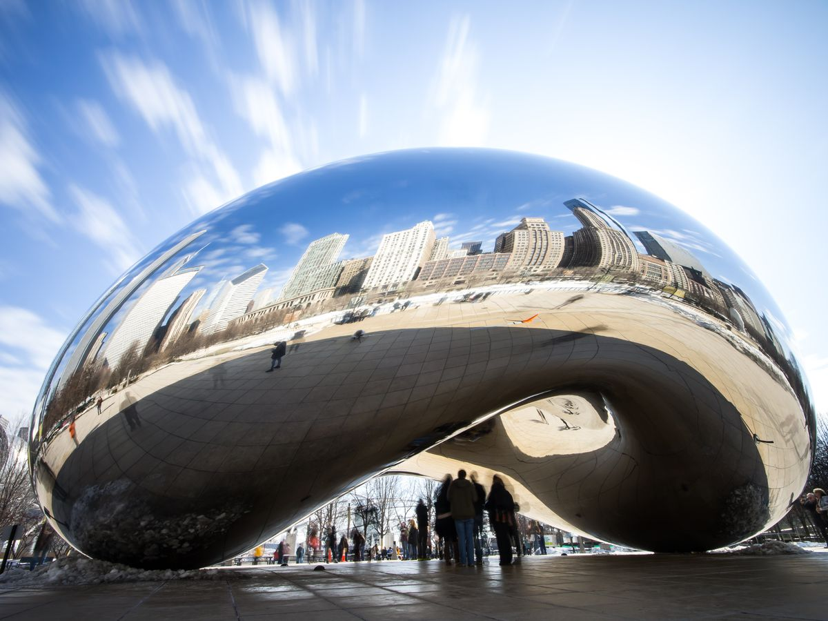 Cloud Gate, also known as The Bean, in Chicago. The sculpture is a mirrored curved shape that sits in a courtyard. It reflects Chicago's skyline.