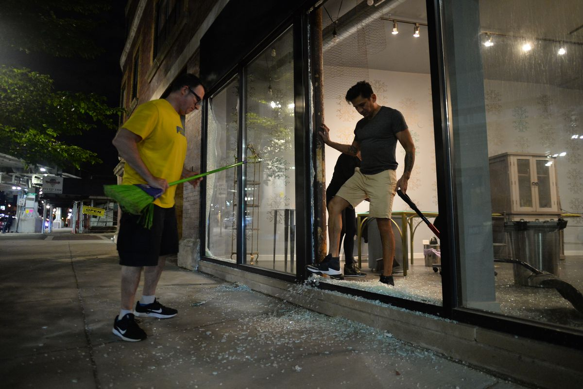 Owners of the Fashion Showroom on North Broadway cleaning up shattered glass as looting continued June 1.