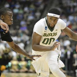 Baylor forward Royce O'Neale (00) drives past Georgia State guard Ryann Green (2) during the first half of an NCAA tournament second round college basketball game, Thursday, March 19, 2015, in Jacksonville, Fla.  (AP Photo/Rick Wilson)