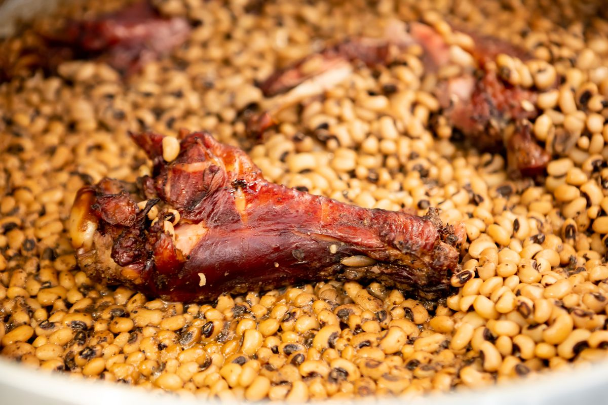 Smoked turkey drumsticks on top of a big pot of black-eyed peas