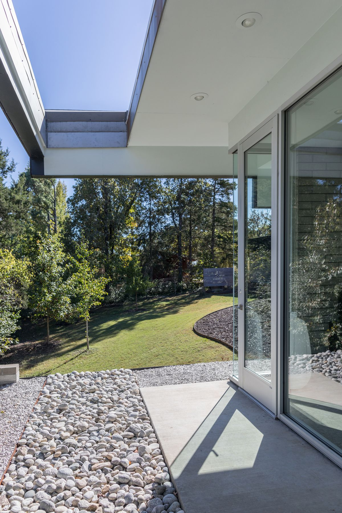 A long overhang over a big bank of glass doors has a rectangular opening in it.
