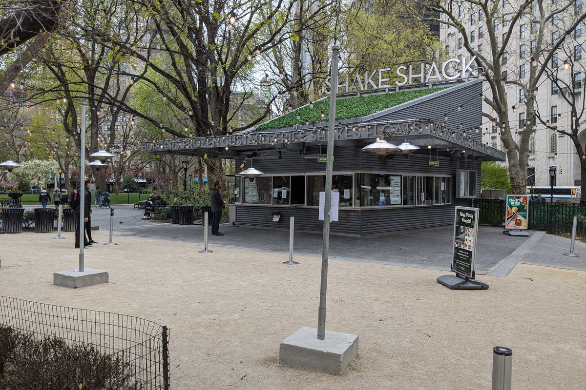 A Shake Shack structure that's located in the middle of a park with gravel paths in front and trees in the back