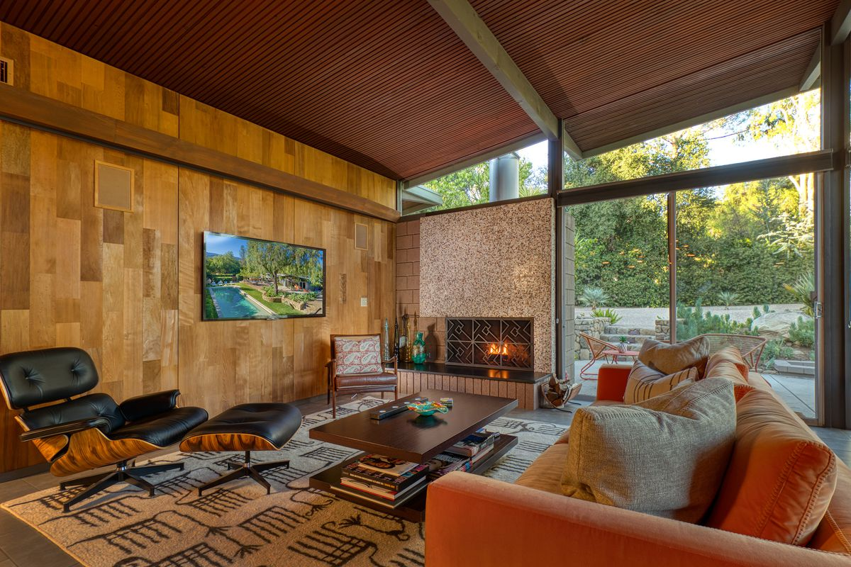 A living room has an Eames chair, a sofa, and a fireplace.
